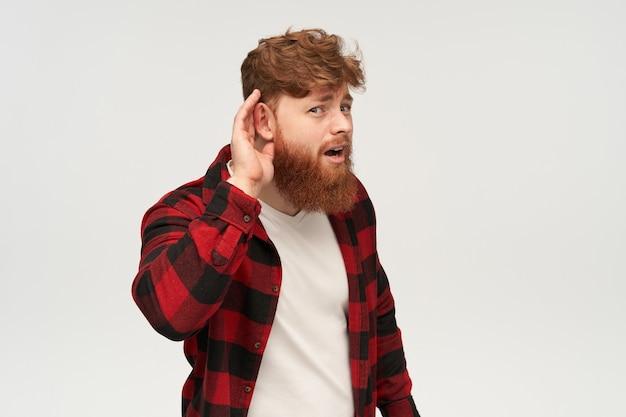 Jonge, bebaarde hipster man met grote rode baard, die iets probeert te horen