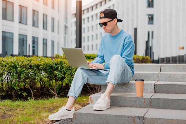 Jonge, bebaarde hipster zakenman staat op straat houdt kopje koffie en maakt gebruik van tablet-pc. moderne glazen gebouw man aan het werk bloggen chatten online sociale media