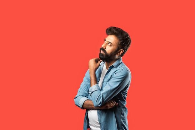 Jonge, bebaarde indiase man die twijfelt en een verwarde gezichtsuitdrukking heeft terwijl hij op rood staat Premium Foto