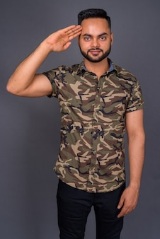 Jonge, bebaarde indiase man tegen grijs