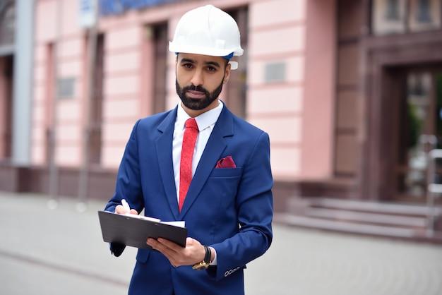 Jonge bebaarde ingenieur maken van aantekeningen op zijn klembord copyspace aan de zijkant