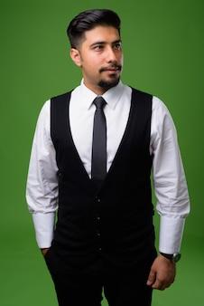 Jonge, bebaarde iraanse zakenman op groen