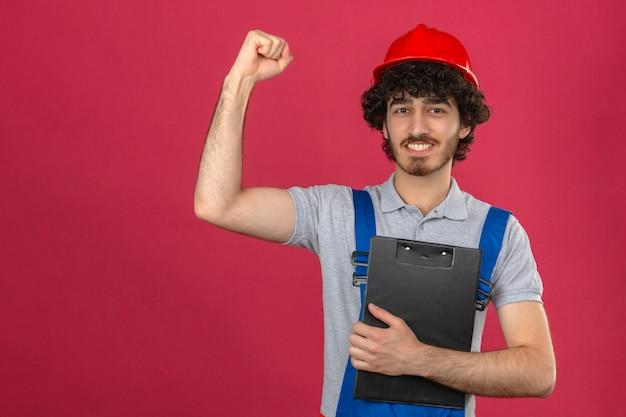 Jonge, bebaarde, knappe bouwer dragen van uniforme bouw en veiligheidshelm klembord verhogen vuist met blij gezicht na overwinning winnaar concept over geïsoleerde roze muur