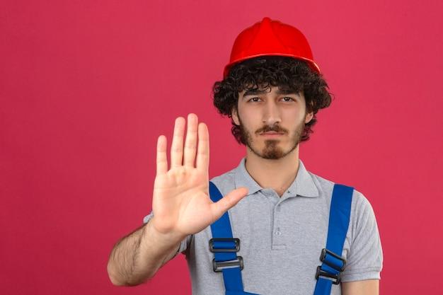 Jonge, bebaarde knappe bouwer dragen van uniforme bouw en veiligheidshelm staan met open hand doen stopbord met ernstige en vol vertrouwen expressie gebaar over geïsoleerde pin