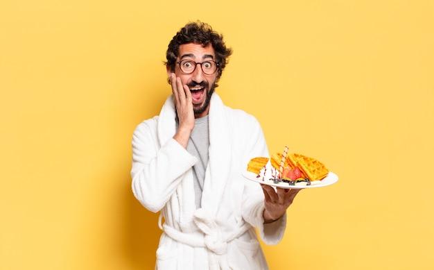 Jonge, bebaarde man badjas dragen en ontbijten Premium Foto