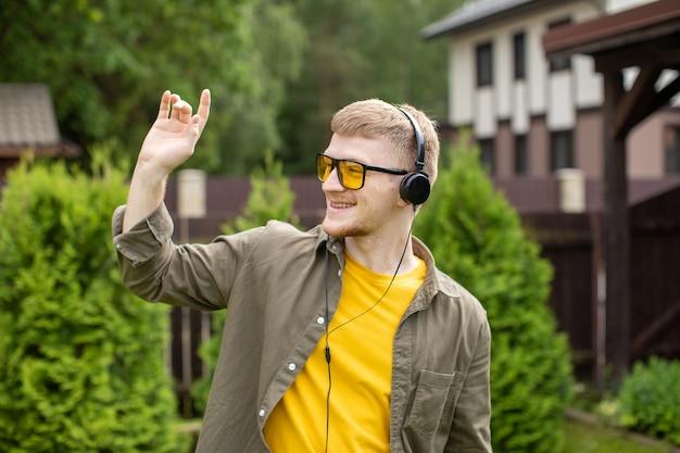 Jonge, bebaarde man begroet iemand met een golf van zijn hand, luisteren naar muziek online via moderne koptelefoon buitenshuis buiten op zonnige zomerdag