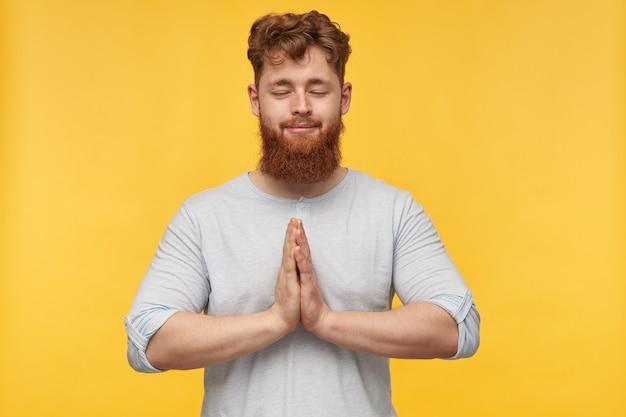 Jonge, bebaarde man blijft kalm, houdt zijn handpalm bij elkaar, ogen gesloten en glimlacht. meditatie na een lange dag op geel.