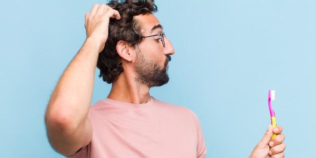 Jonge, bebaarde man denken of twijfelen, hoofd krabben, zich verbaasd en verward voelen, achter- of achteraanzicht