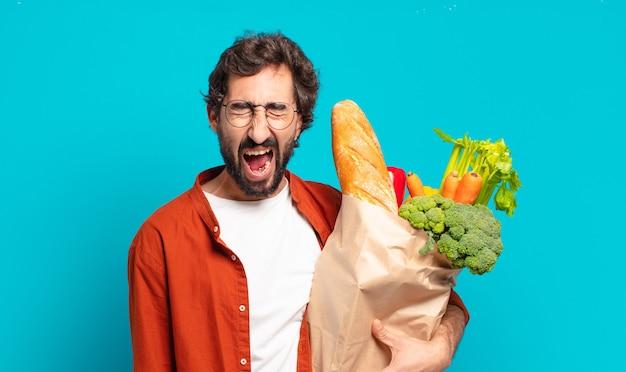 Jonge, bebaarde man die agressief schreeuwt, erg boos, gefrustreerd, verontwaardigd of geïrriteerd kijkt, nee schreeuwt en een zak met groenten vasthoudt