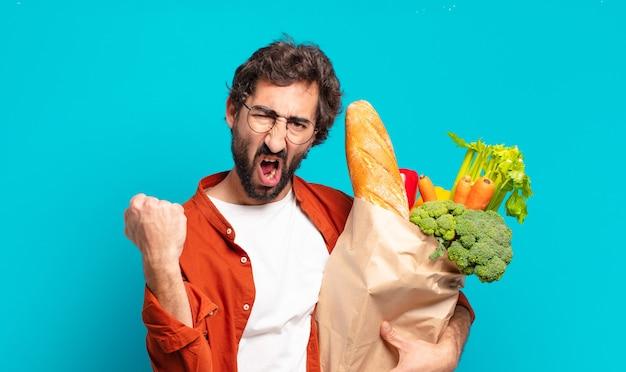 Jonge, bebaarde man die agressief schreeuwt met een boze uitdrukking of met gebalde vuisten om succes te vieren en een zak met groenten vast te houden