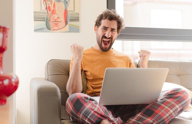 Jonge, bebaarde man die agressief schreeuwt met een boze uitdrukking of met gebalde vuisten viert succes en zit met een laptop