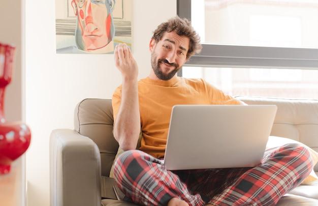 Jonge, bebaarde man die capice of geldgebaar maakt en je vertelt dat je je schulden moet betalen en met een laptop zit