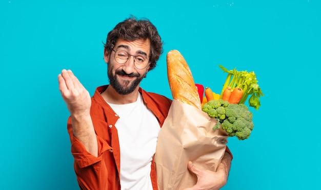 Jonge, bebaarde man die capice of geldgebaar maakt en u vertelt uw schulden te betalen! en met een zak met groenten