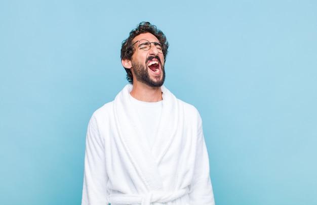 Jonge, bebaarde man die een badjas draagt die woedend schreeuwt, agressief schreeuwt, er gestrest en boos uitziet