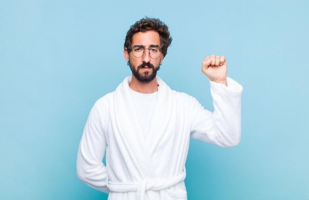 Jonge, bebaarde man die een badjas draagt die zich ernstig voelt