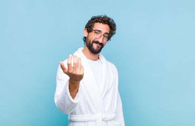 Jonge, bebaarde man die een badjas draagt die zich gelukkig, succesvol en zelfverzekerd voelt, een uitdaging aangaat en zegt: kom maar op! of je verwelkomen