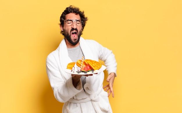 Jonge, bebaarde man die een badjas draagt en aan het ontbijten is