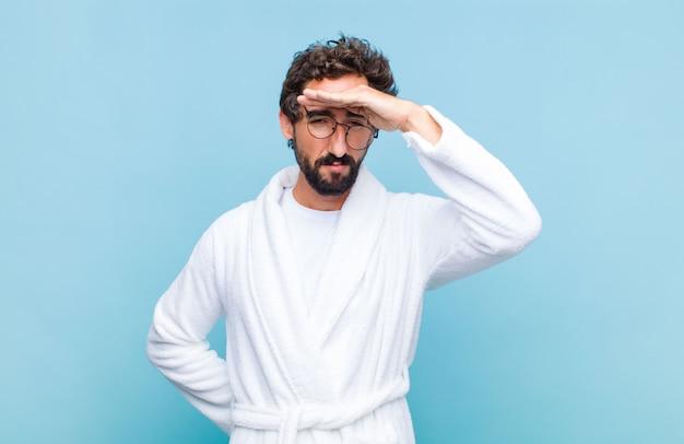 Jonge, bebaarde man die een badjas draagt en er verbijsterd en verbaasd uitziet, met de hand over het voorhoofd ver weg kijkt, kijkt of zoekt