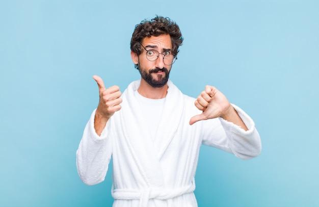 Jonge, bebaarde man die een badjas draagt en zich verward, geen idee en onzeker voelt, het goede en slechte afwegen in verschillende opties of keuzes
