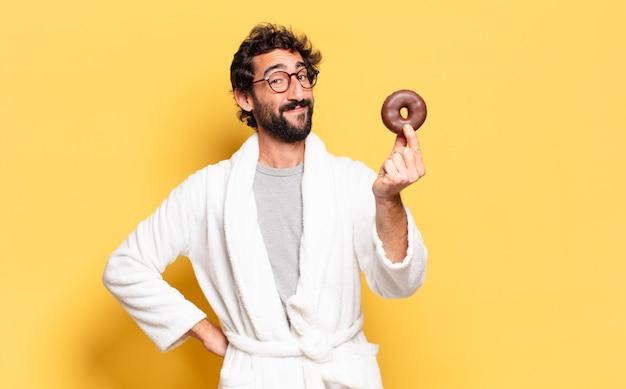 Jonge, bebaarde man die een badjas draagt met een chocoladedoughnut