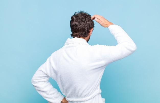 Jonge, bebaarde man die een badjas draagt, voelt zich geen idee en verward, denkt een oplossing, met de hand op de heup en de andere op het hoofd, achteraanzicht