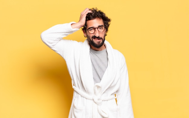 Jonge, bebaarde man die een badjas draagt