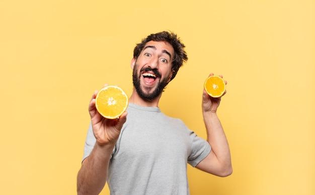 Jonge, bebaarde man die een gelukkige uitdrukking op dieet heeft en een sinaasappel vasthoudt
