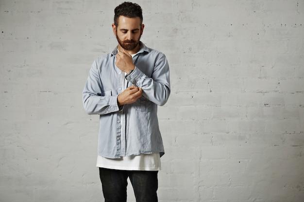 Jonge, bebaarde man die een lichtblauw denimoverhemd en zwarte spijkerbroek draagt die zijn overhemdskoker op witte bakstenen muur losknopen