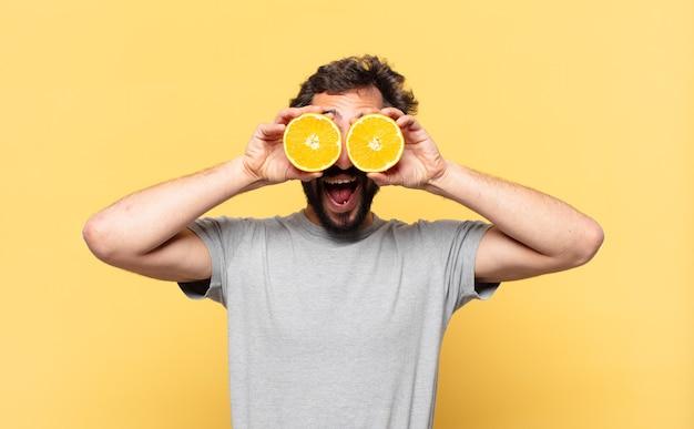 Jonge, bebaarde man die een verbaasde uitdrukking volgt en een sinaasappel vasthoudt