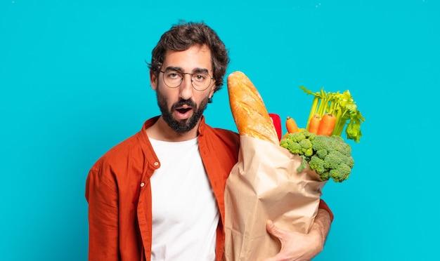 Jonge, bebaarde man die erg geschokt of verrast kijkt, met open mond staart en wauw zegt en een groentezak vasthoudt