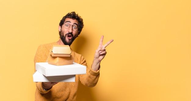 Jonge, bebaarde man die fastfood heeft weggehaald met een kopieerruimte