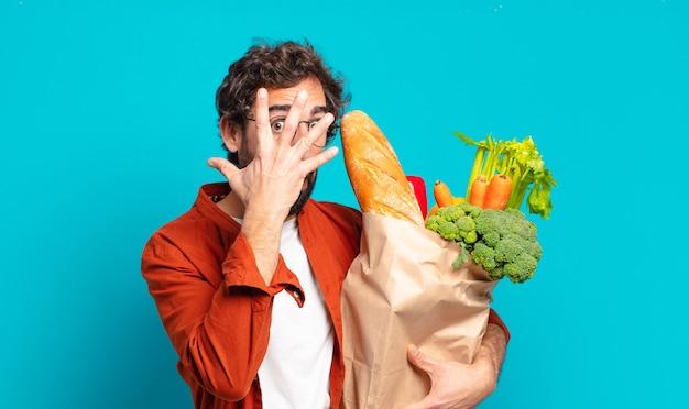 Jonge, bebaarde man die geschokt, bang of doodsbang kijkt, het gezicht bedekt met de hand en tussen de vingers gluurt en een zak met groenten vasthoudt