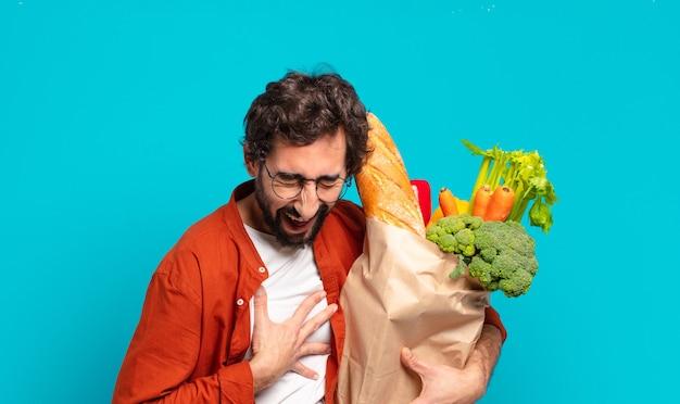 Jonge, bebaarde man die hardop lacht om een of andere hilarische grap, zich gelukkig en opgewekt voelt, plezier heeft en een zak met groenten vasthoudt