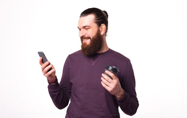 Jonge, bebaarde man die lacht kijkt in zijn telefoon en houdt een kopje met warme drank