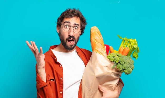 Jonge, bebaarde man die met de handen in de lucht schreeuwt, zich woedend, gefrustreerd, gestrest en boos voelt en een zak met groenten vasthoudt