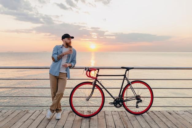 Jonge, bebaarde man die op de fiets reist bij zonsondergang op zee