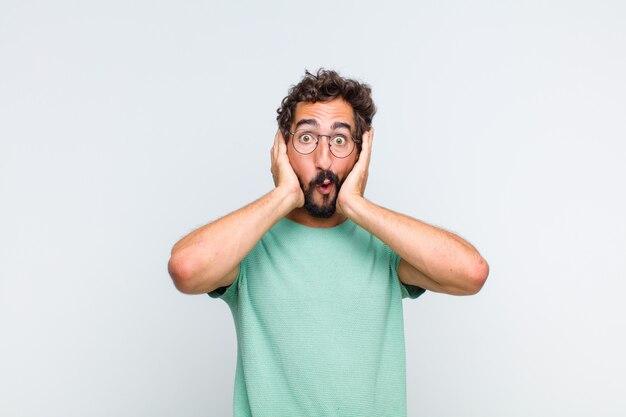 Jonge, bebaarde man die opgewonden en verrast kijkt, met open mond en beide handen op het hoofd, zich een gelukkige winnaar voelt