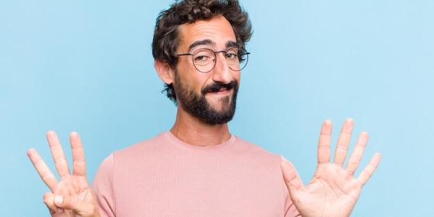 Jonge, bebaarde man die vriendelijk glimlacht en kijkt, nummer acht of achtste met vooruit hand toont, aftellend