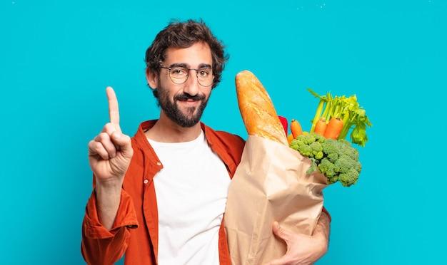 Jonge, bebaarde man die vriendelijk glimlacht en kijkt, nummer één toont of eerst met vooruit hand, aftellend en een groentenzak vasthoudt