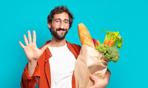 Jonge, bebaarde man die vriendelijk glimlacht en kijkt, nummer vijf of vijfde met vooruit hand toont, aftellend en een groentenzak vasthoudt
