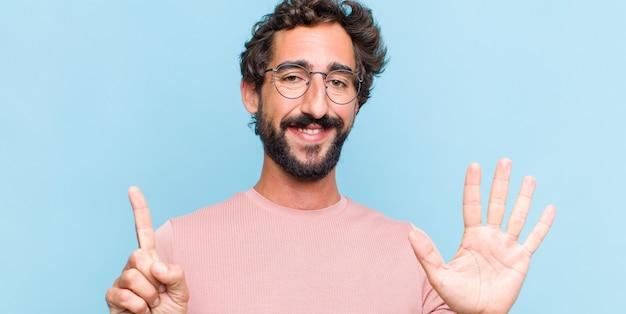 Jonge, bebaarde man die vriendelijk glimlacht en kijkt, nummer zes of zesde met vooruit hand toont, aftellend