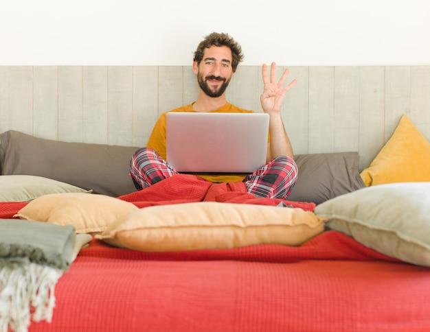 Jonge, bebaarde man die vriendelijk glimlacht kijkt en nummer vier of vierde toont met vooruit aftellende hand