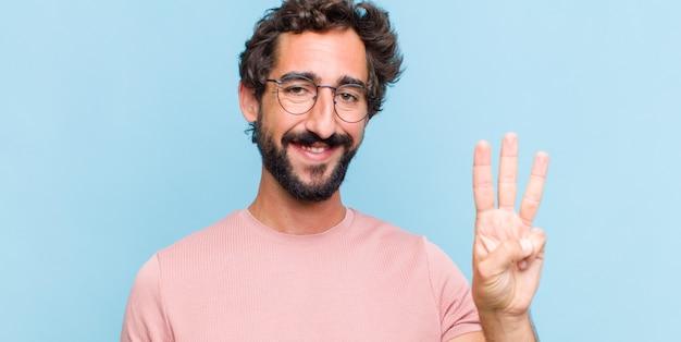 Jonge, bebaarde man die vriendelijk glimlacht kijkt, nummer drie of derde met vooruit hand toont, aftellend