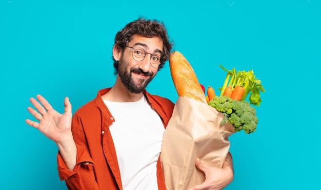 Jonge, bebaarde man die vrolijk en opgewekt lacht, hand zwaait, je verwelkomt en begroet, of afscheid neemt en een zak met groenten vasthoudt