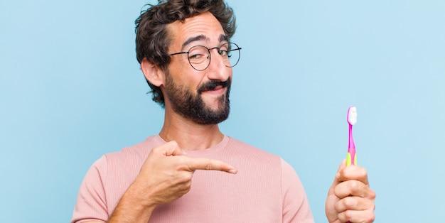 Jonge, bebaarde man die vrolijk glimlacht en naar kopie ruimte op de handpalm aan de zijkant wijst, een object laat zien of er reclame voor maakt