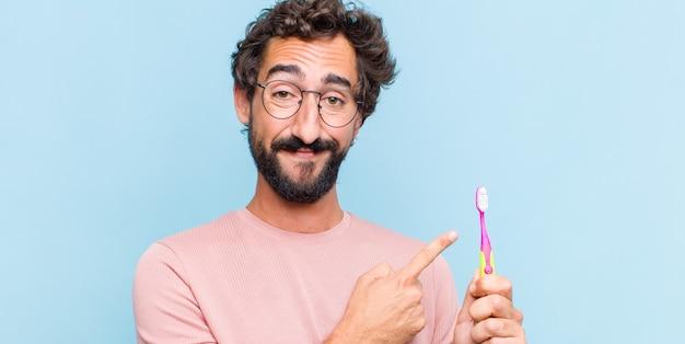 Jonge, bebaarde man die vrolijk lacht, zich gelukkig voelt en naar de zijkant en naar boven wijst, object in kopie ruimte toont