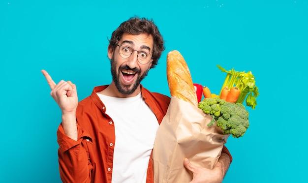 Jonge, bebaarde man die zich als een blij en opgewonden genie voelt na het realiseren van een idee, vrolijk de vinger op te steken, eureka! en met een zak met groenten