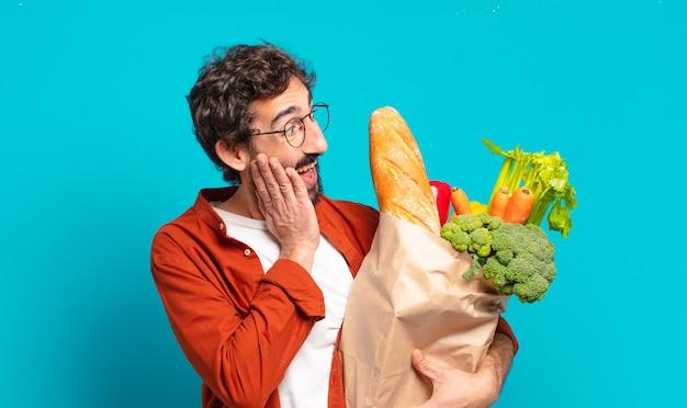 Jonge, bebaarde man die zich blij, opgewonden en verrast voelt, naar de zijkant kijkt met beide handen op het gezicht en een zak met groenten vasthoudt