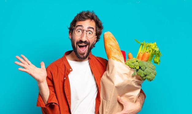 Jonge, bebaarde man die zich blij, opgewonden, verrast of geschokt voelt, glimlacht en verbaasd is over iets ongelooflijks en een zak met groenten vasthoudt