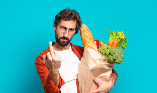 Jonge, bebaarde man die zich boos, geïrriteerd, rebels en agressief voelt, de middelvinger omdraait, terugvecht en een zak met groenten vasthoudt